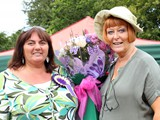 Jean Reid presenting a bouquet of flowers to Bernie McKenna for all her hard work organising the show